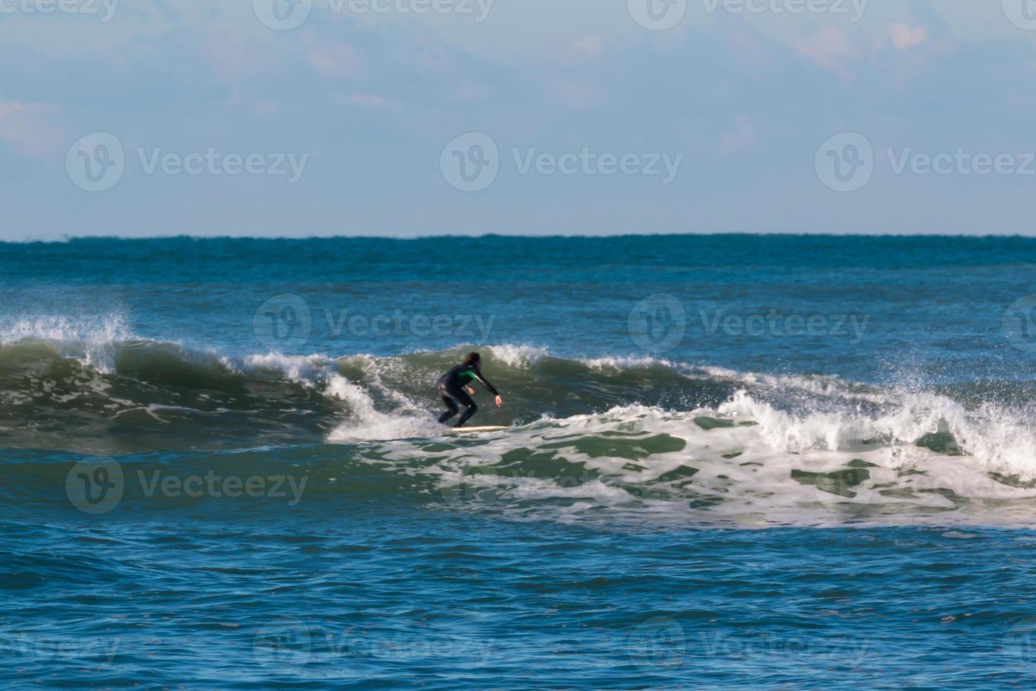 combinaison surfeuse noire surfant sur la vague photo