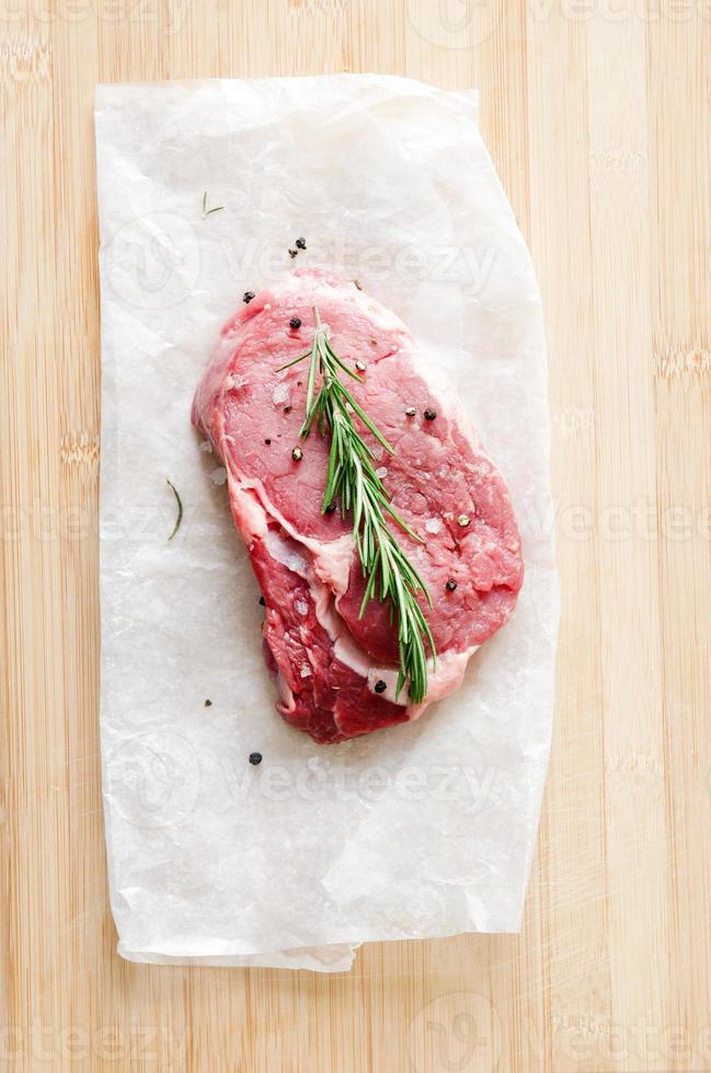 steak cru sur une surface en bois avec du sel et du poivre photo