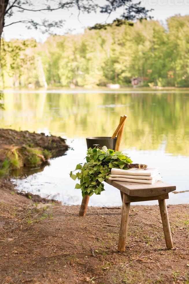 paysage d'été finlandais et objets sauna sur banc au bord du lac. photo