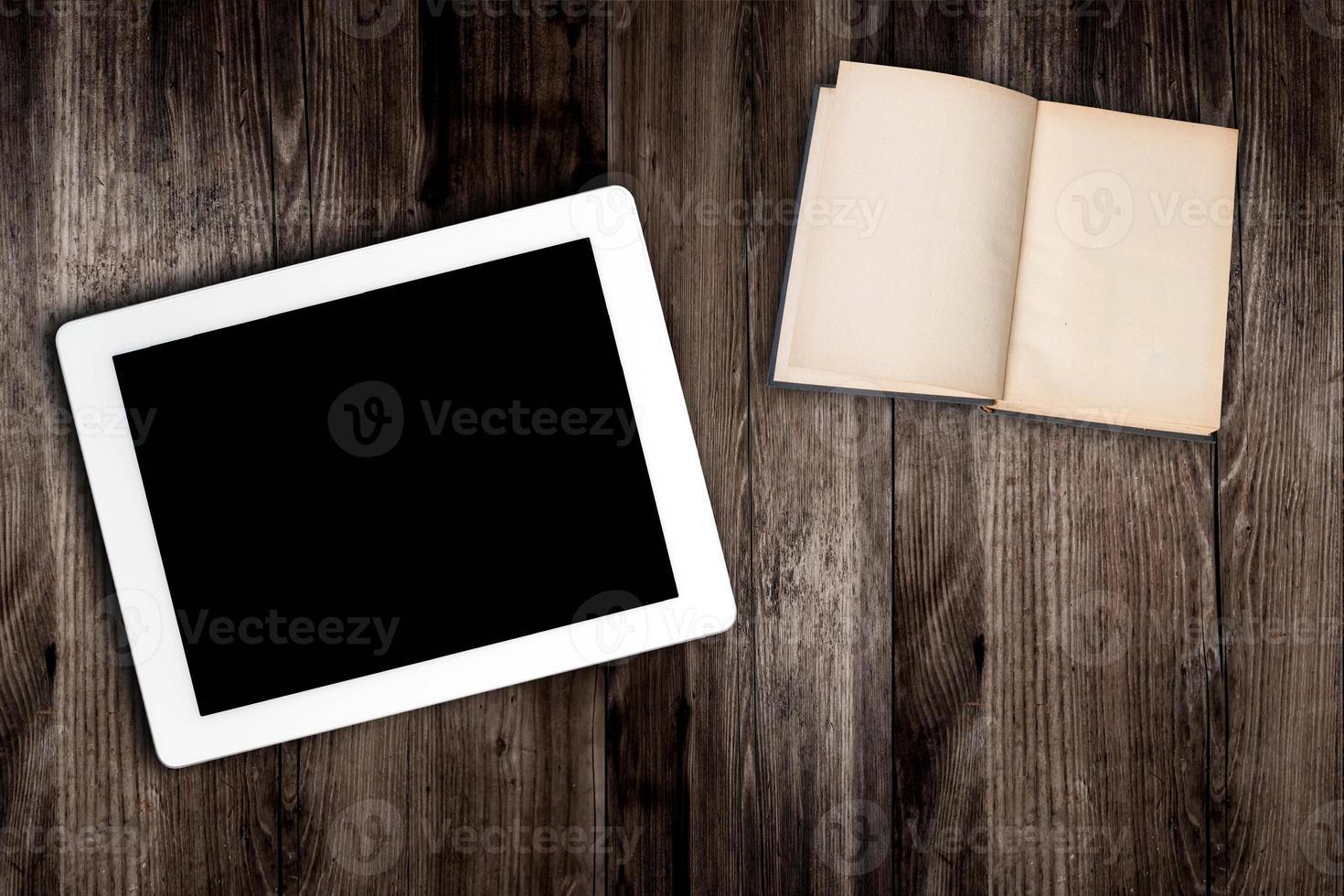 ordinateur tablette et livre sur la vieille table en bois photo