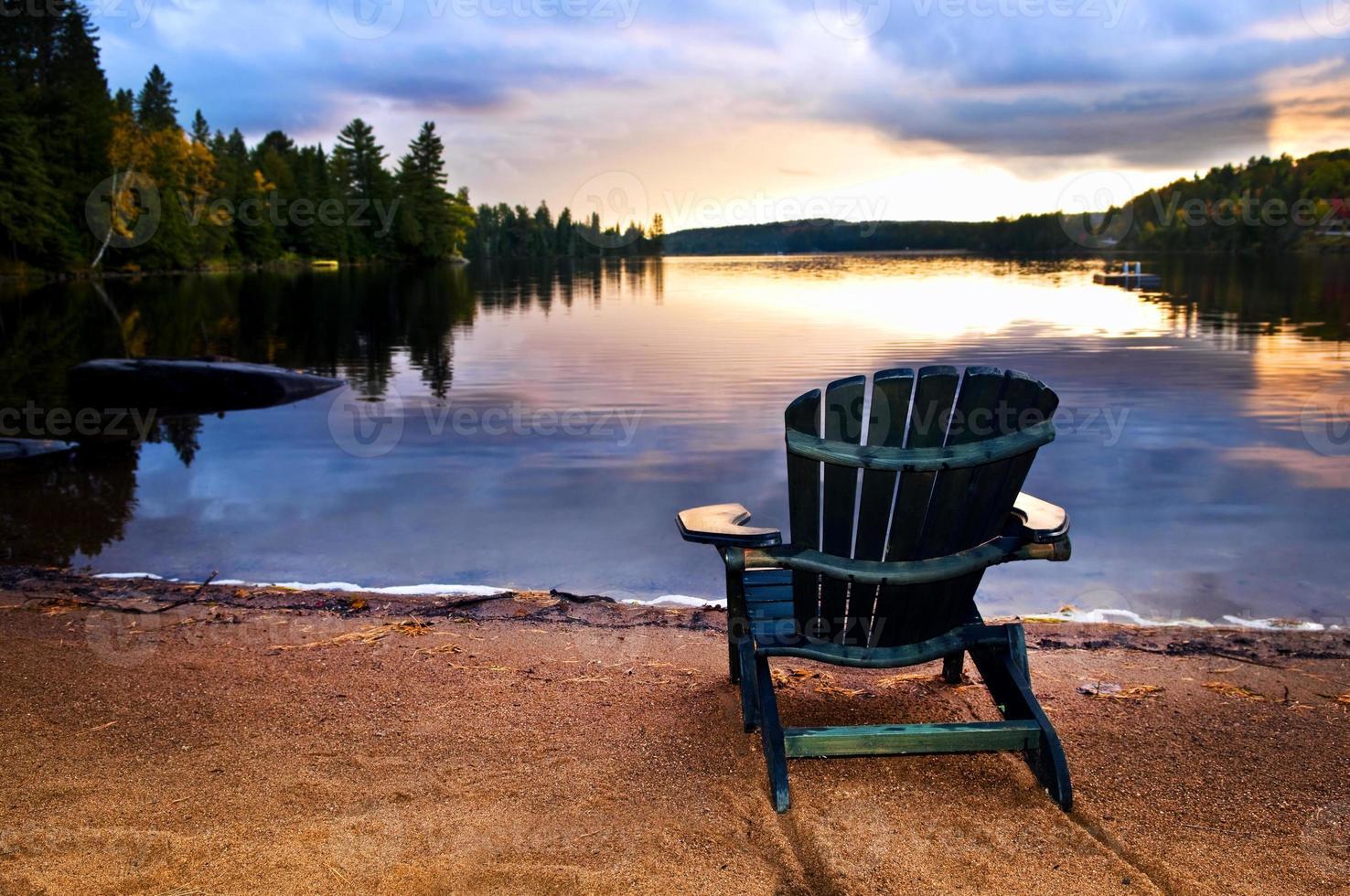 chaise en bois au coucher du soleil sur la plage photo