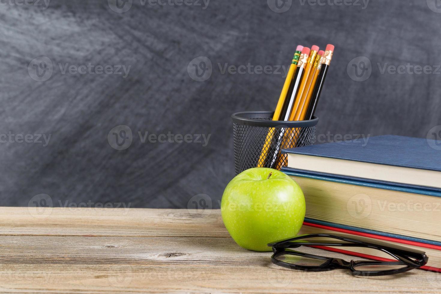 vieux bureau en bois avec pomme verte et matériel de lecture photo