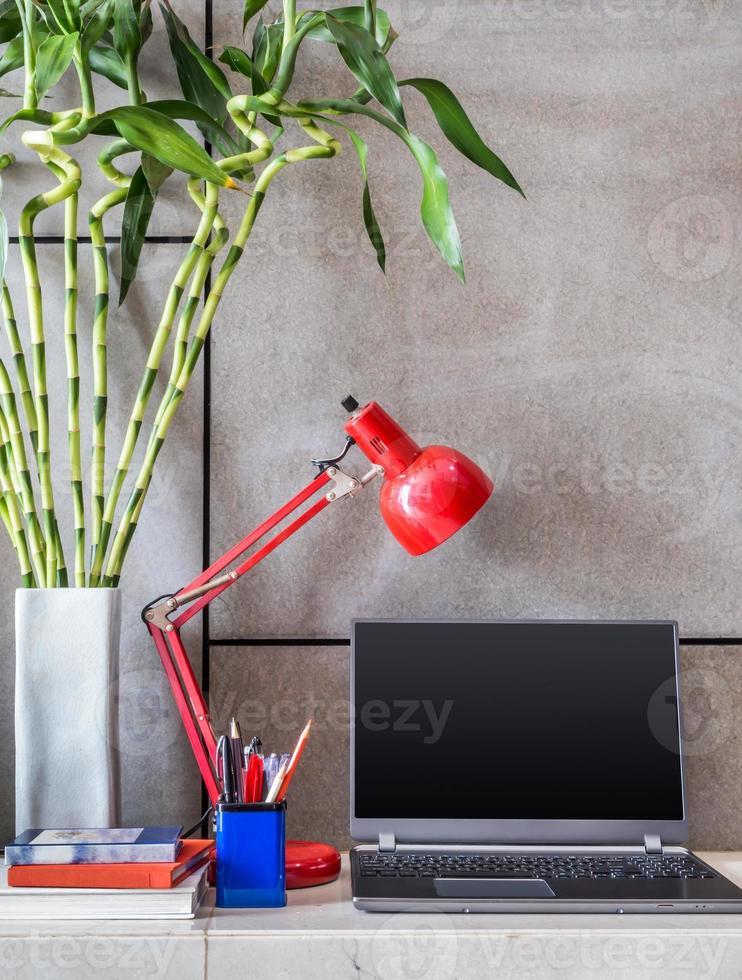 ordinateur portable, lampe avec vase de bambou porte-bonheur dans une chambre moderne photo