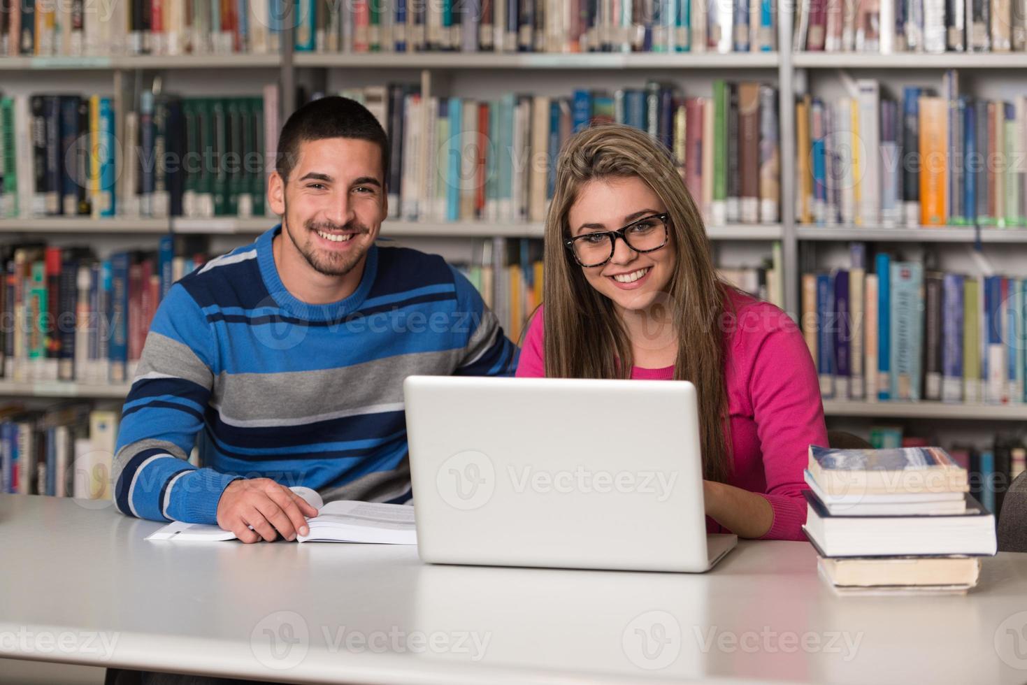 jeunes étudiants utilisant leur ordinateur portable dans une bibliothèque photo