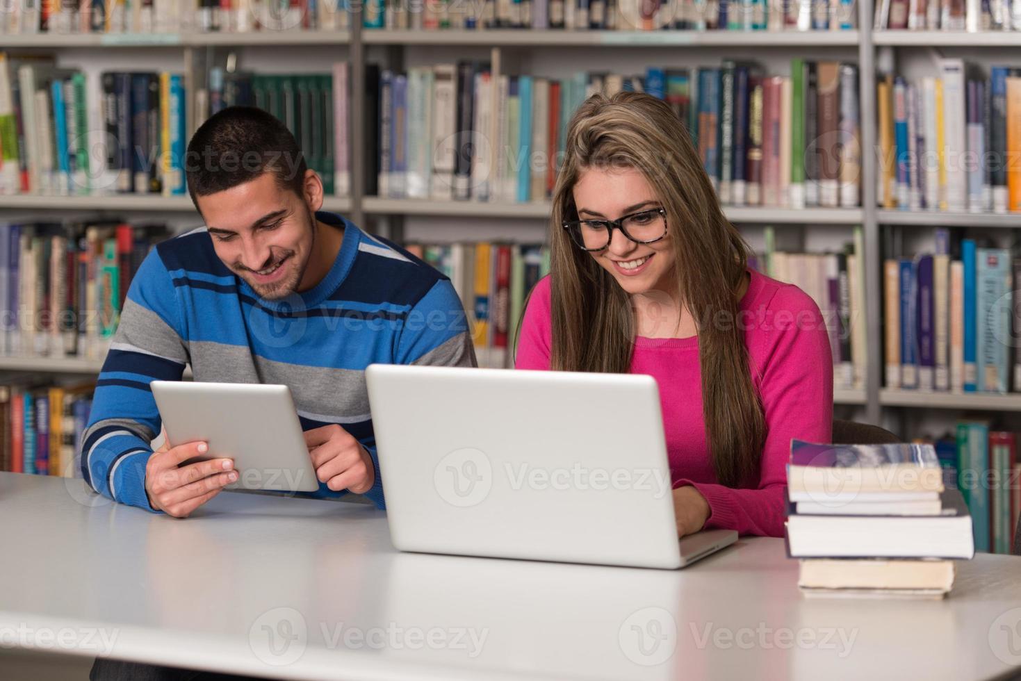 jeunes étudiants utilisant un ordinateur portable et une tablette dans une bibliothèque photo