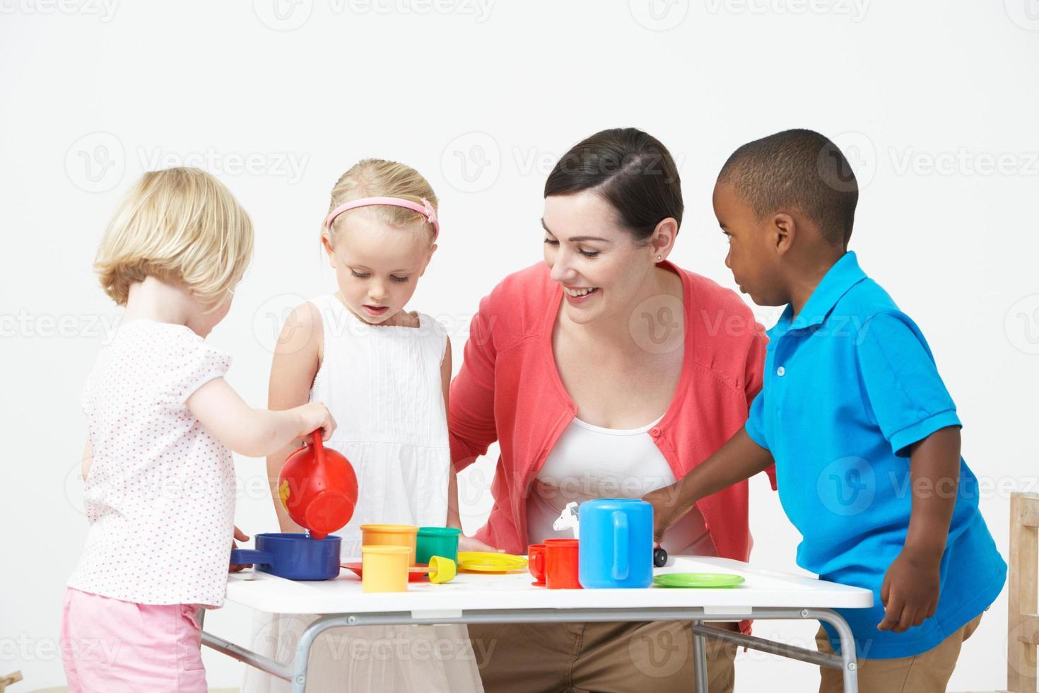 enfants d'âge préscolaire bénéficiant d'un goûter avec le professeur photo