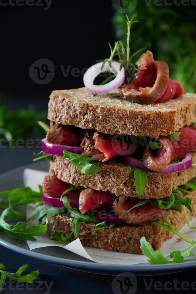 sandwich au pain aux céréales avec rôti de boeuf, oignon et roquette. photo