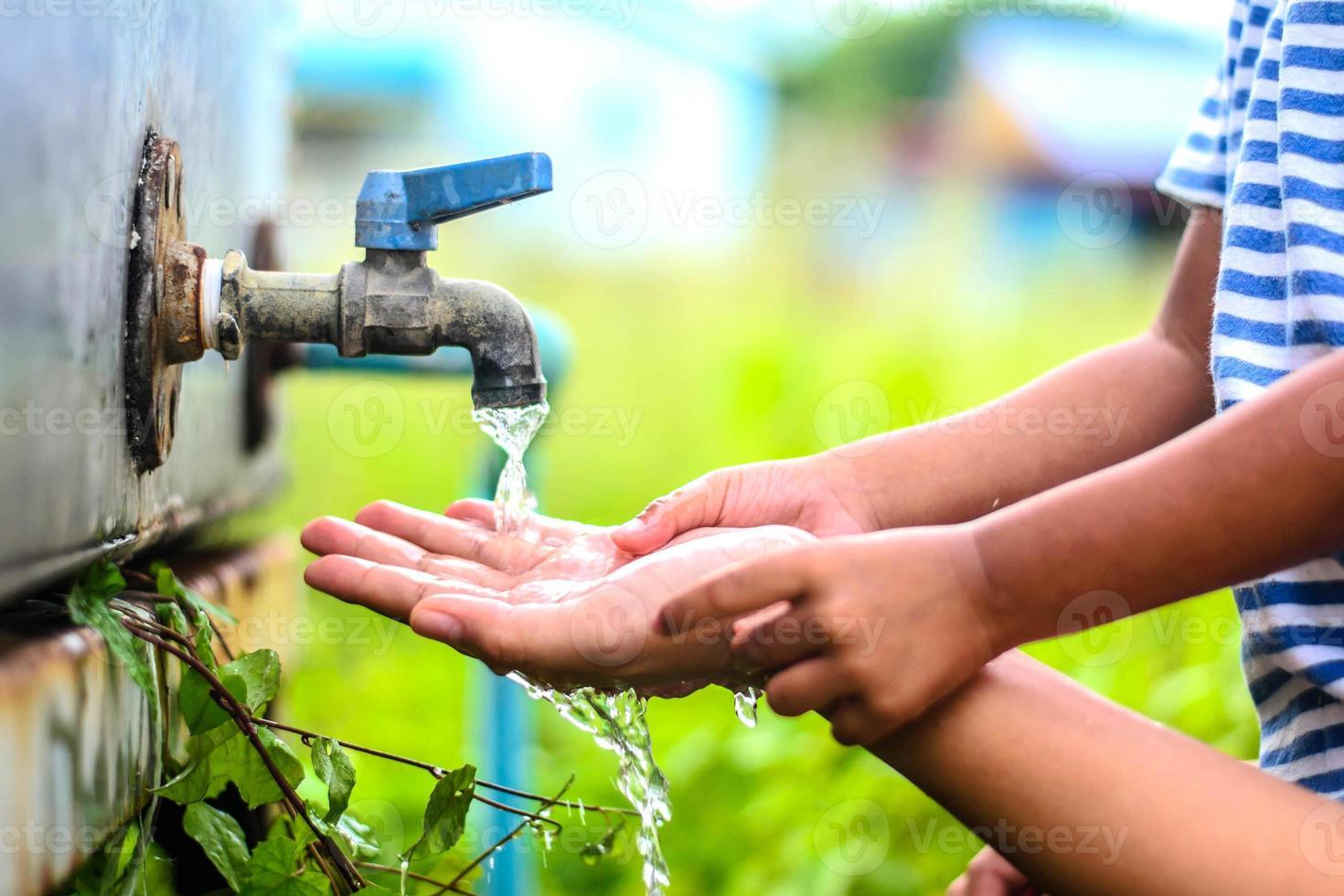 enfant se laver les mains avec la mère, point de mise au point sélective. photo