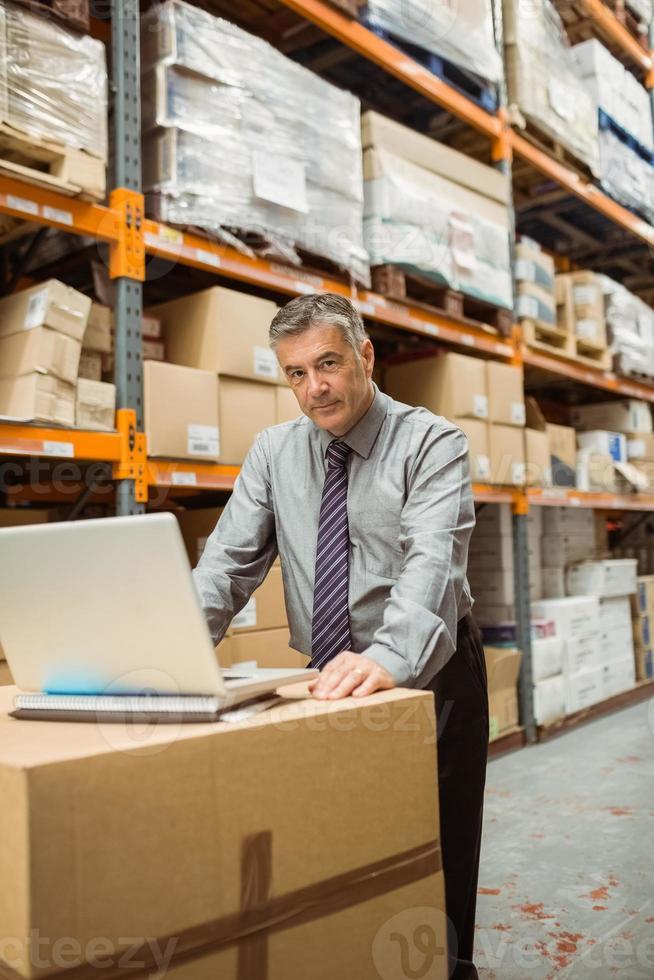 gestionnaire d'entrepôt concentré travaillant sur ordinateur portable photo
