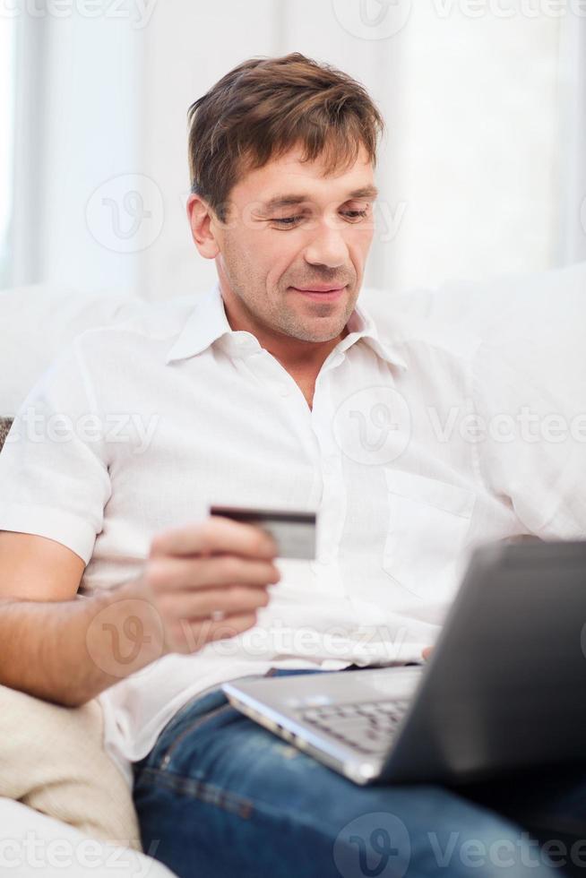 homme avec ordinateur portable et carte de crédit à la maison photo