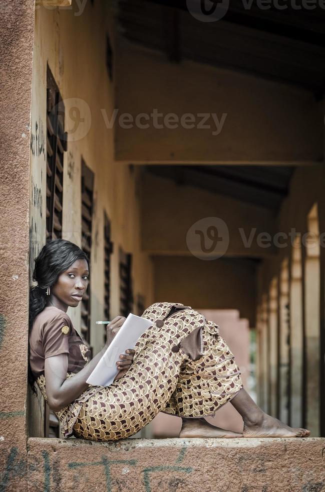 symbole de l'éducation africaine: femme noire écrit des notes de travail à domicile photo