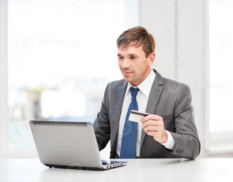 homme avec ordinateur portable et carte de crédit au bureau photo