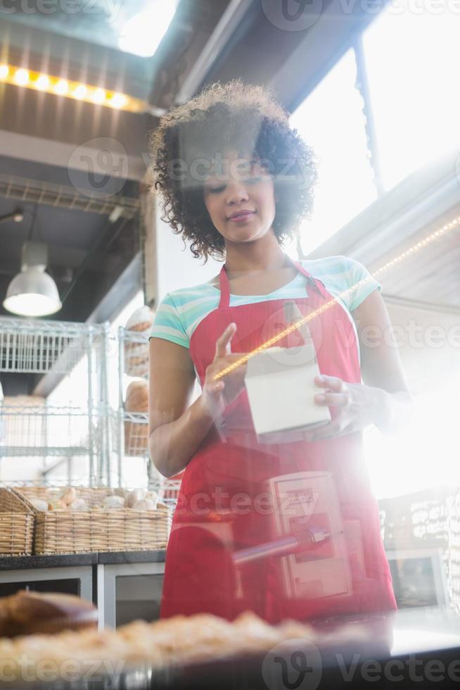 employé en tablier rouge tenant la boîte photo