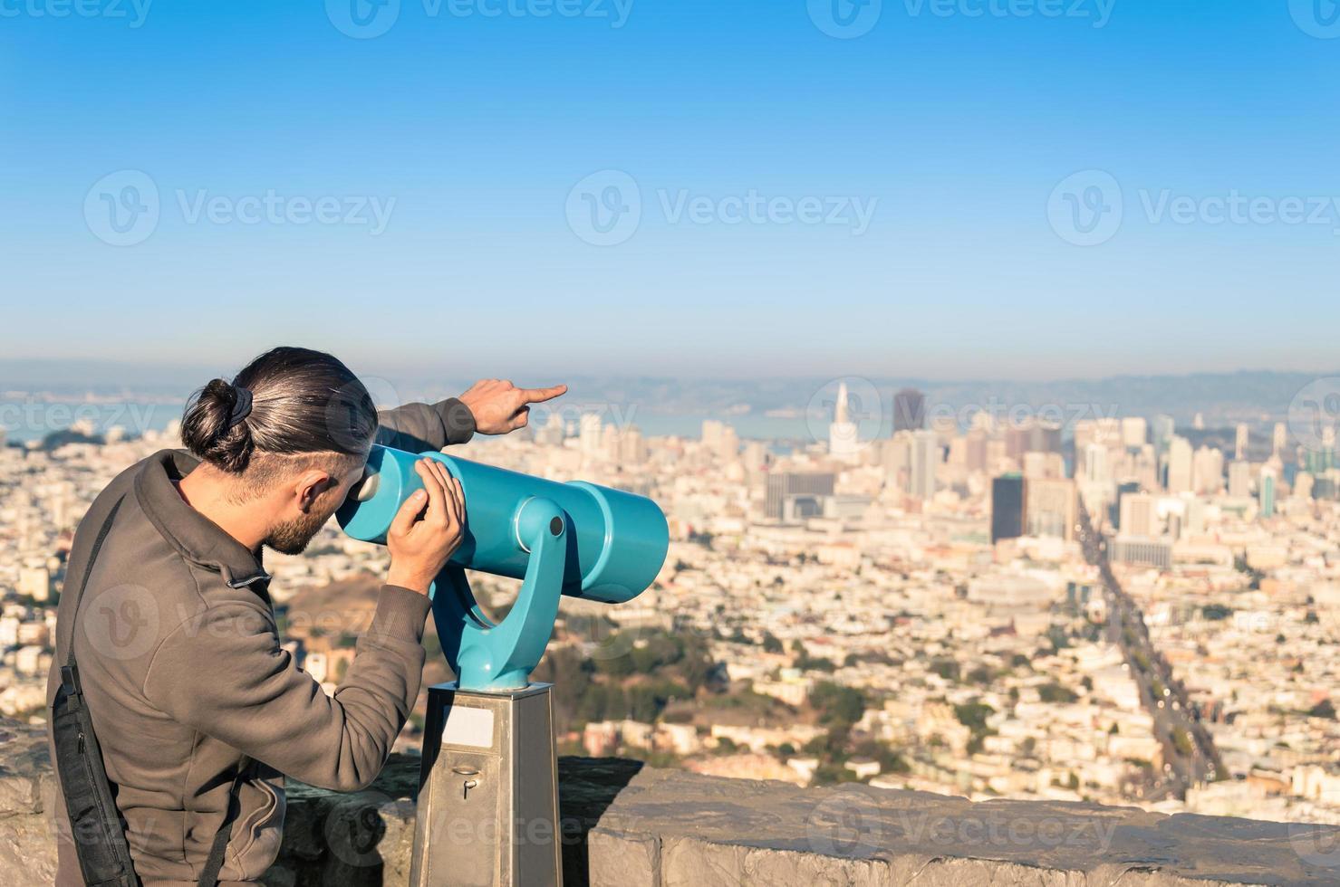 Homme regardant le centre-ville de francisco sur des jumelles de Twin Peaks photo