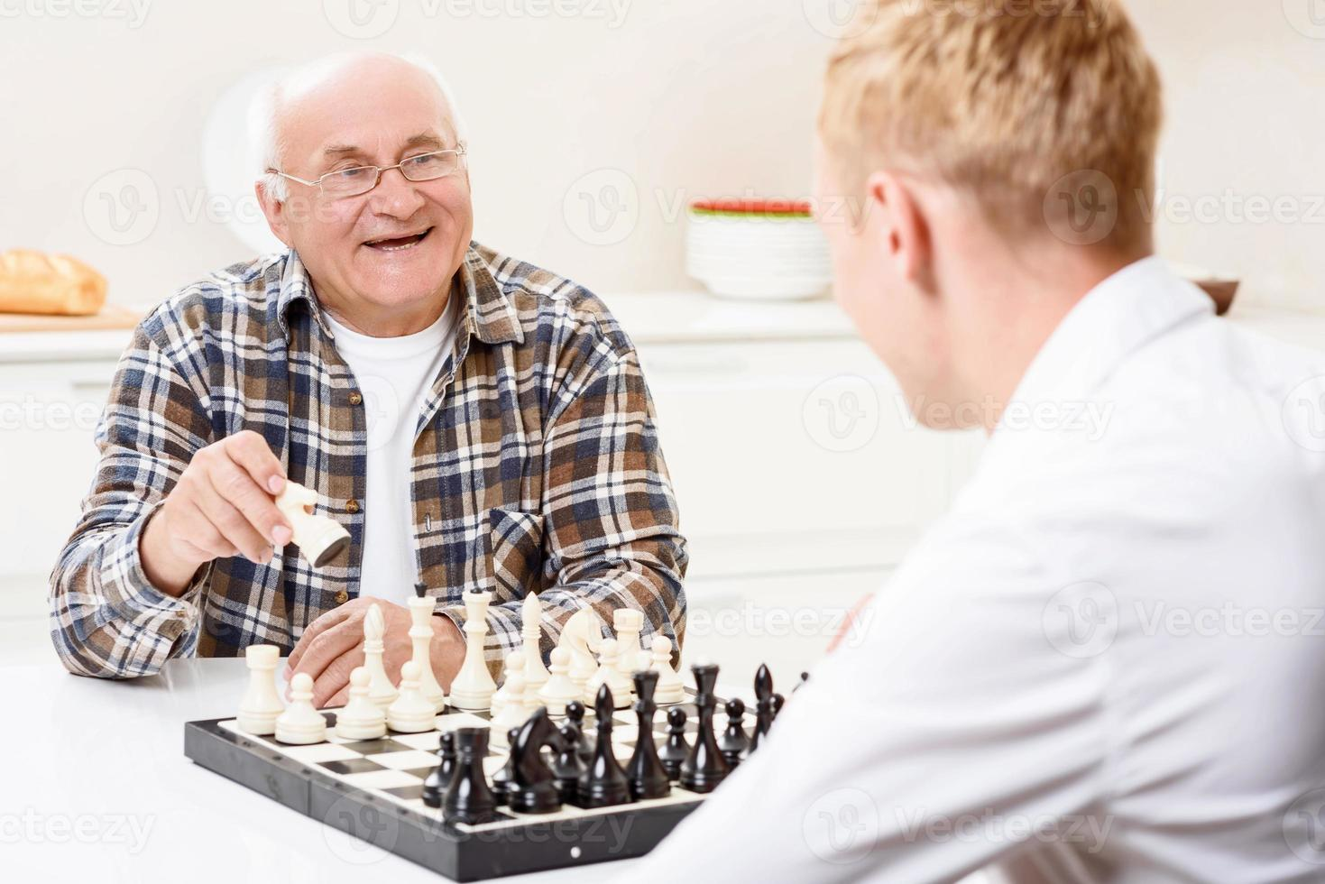 petit-fils et grand-père jouant aux échecs dans la cuisine photo
