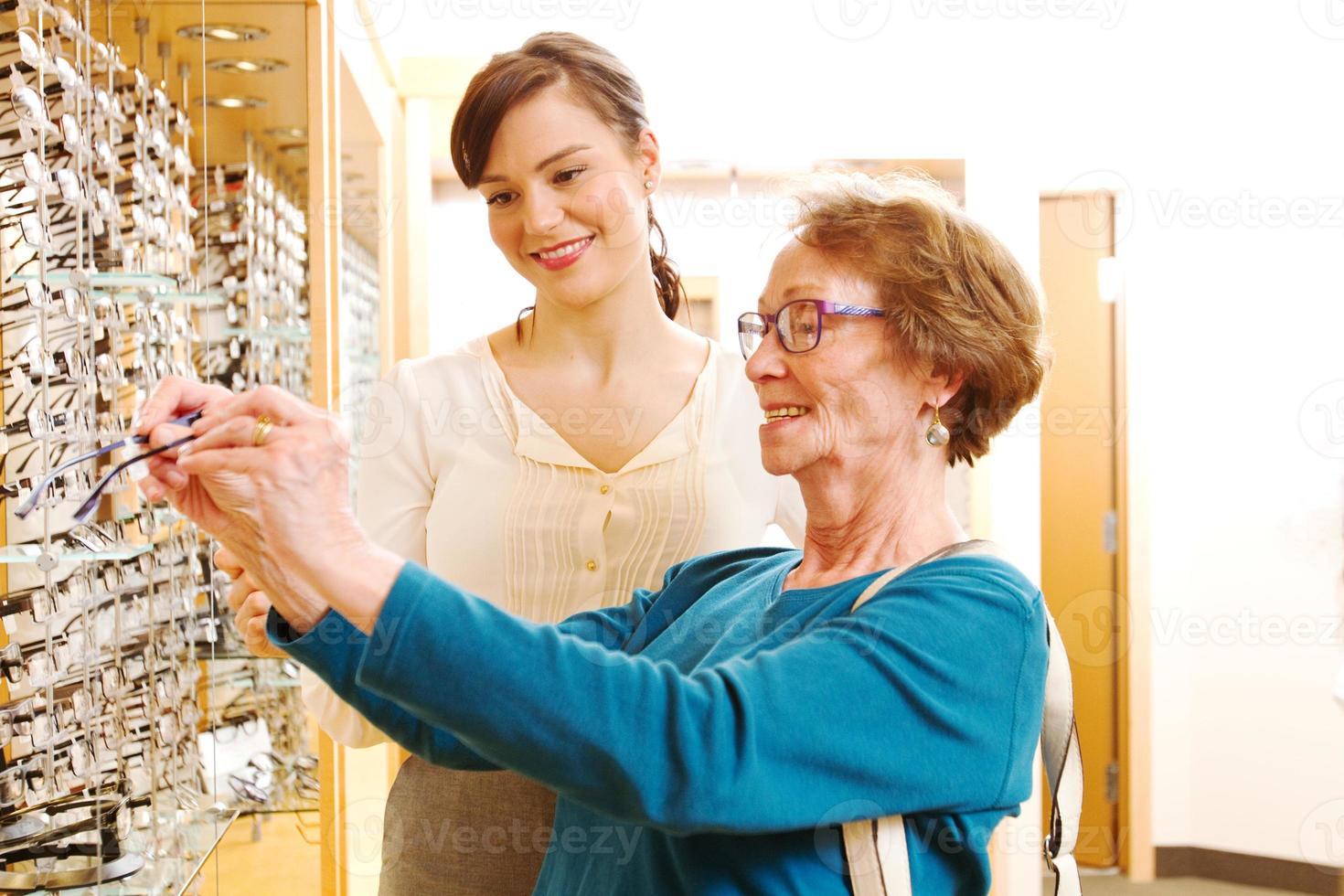 opticien aidant une dame âgée avec des lunettes photo