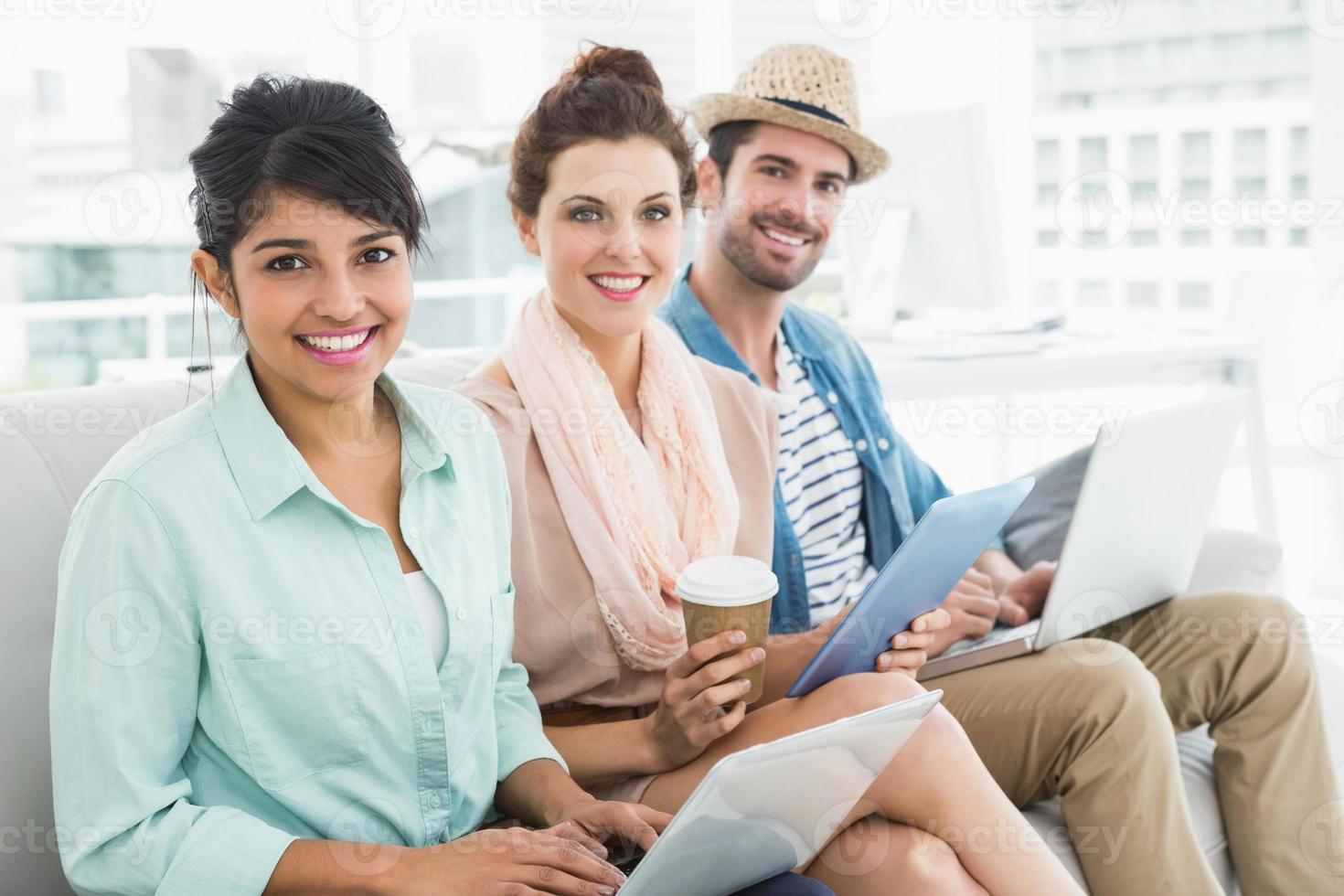 travail d'équipe souriant assis sur un canapé en regardant la caméra photo