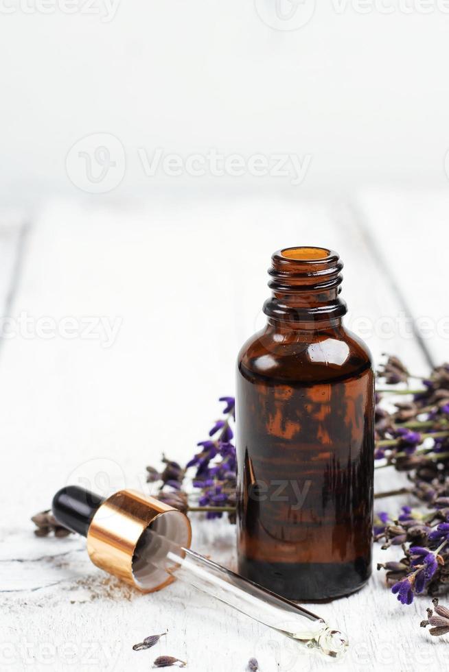lavande sèche et huile sur une table en bois blanc photo