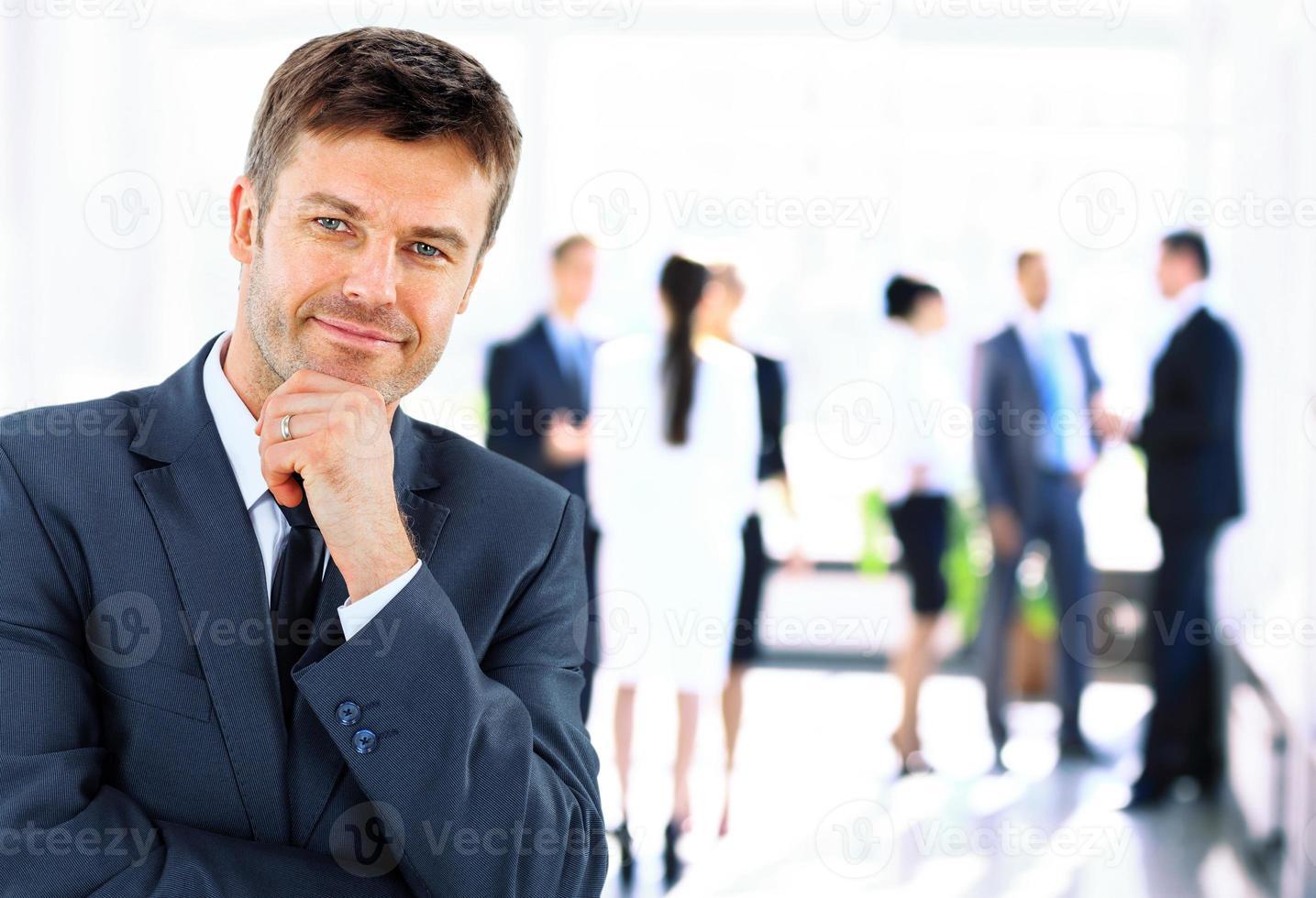 gestionnaire souriant mature suivi de jeunes gens d'affaires photo