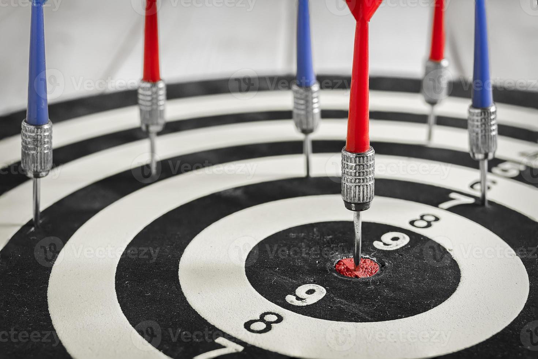 Flèche rouge fléchette frapper dans le centre cible du jeu de fléchettes photo