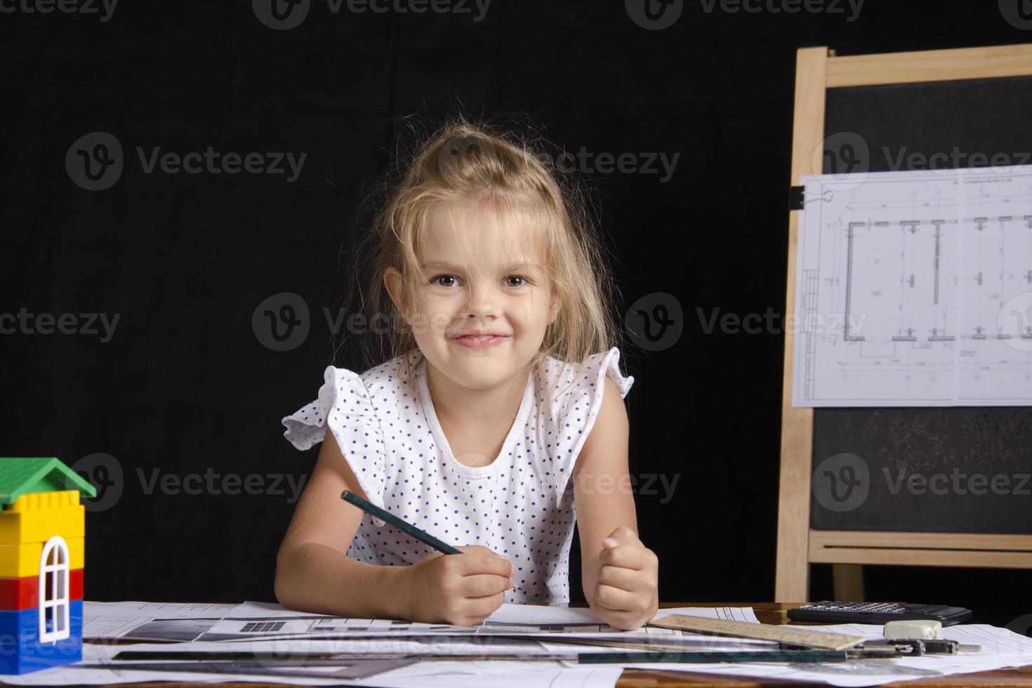 fille-architecte assis derrière le bureau et regarde dans le cadre photo