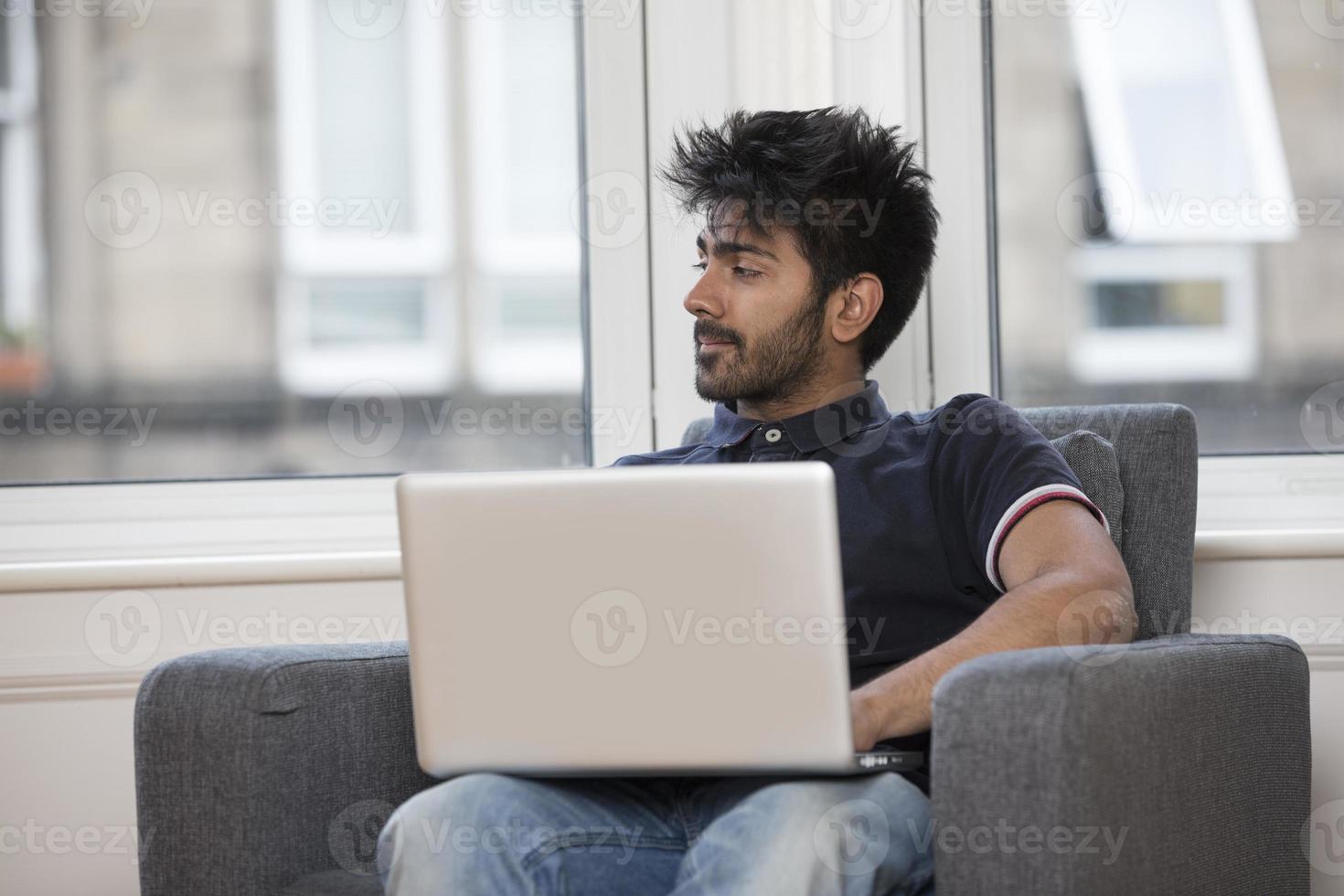 homme asiatique à la maison à l'aide d'un ordinateur portable. photo