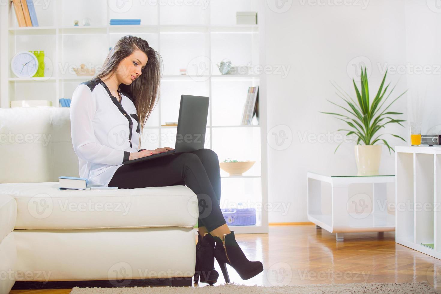 jolie jeune femme à l'aide de son ordinateur portable à la maison photo