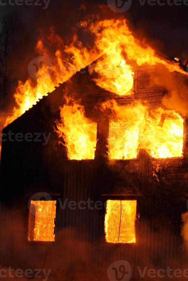 une maison en flammes avec des flammes qui sortent des fenêtres photo