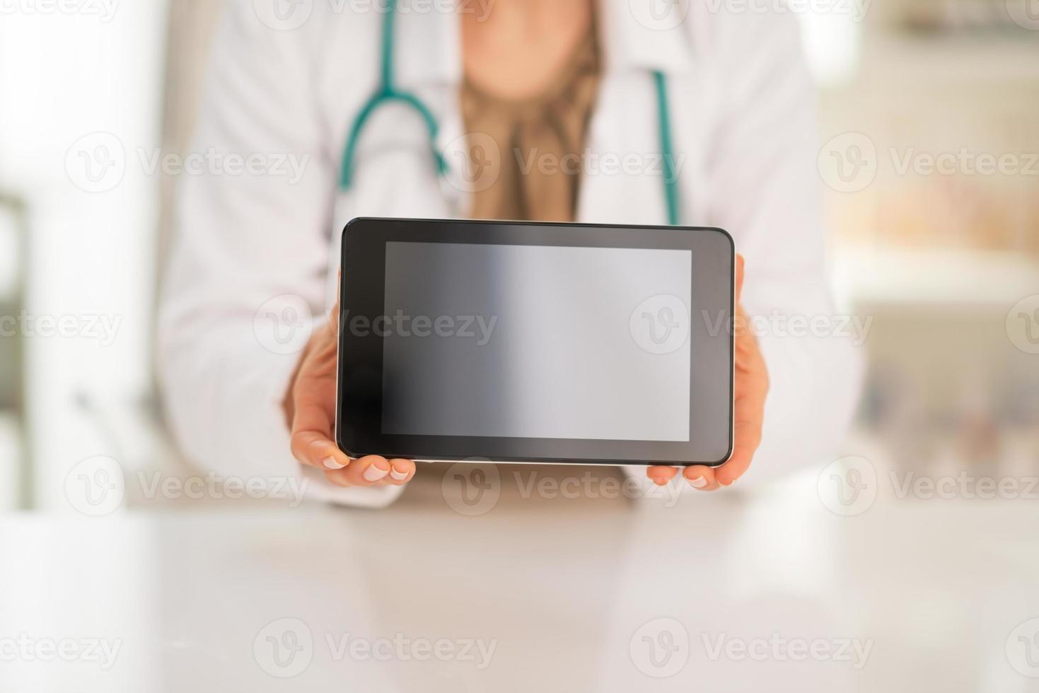 Gros plan sur la femme médecin montrant l'écran vierge du tablet pc photo