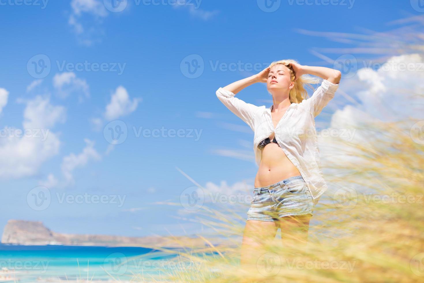 femme heureuse gratuite, profitant du soleil en vacances. photo