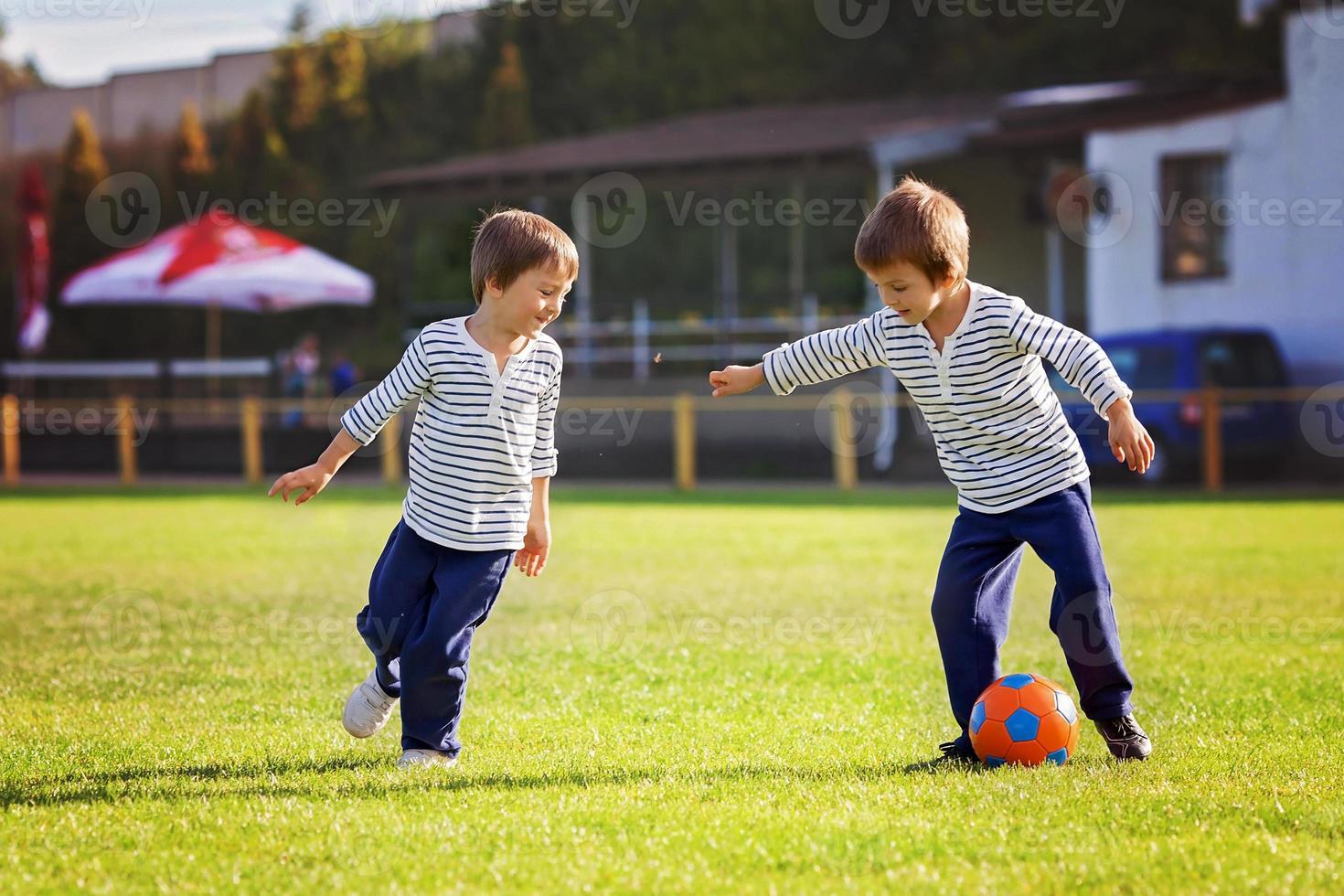 deux mignons petits garçons, jouer au football photo