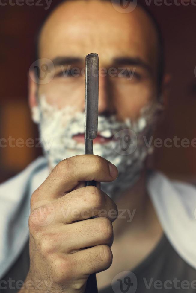 jeune homme tenant un rasoir droit photo