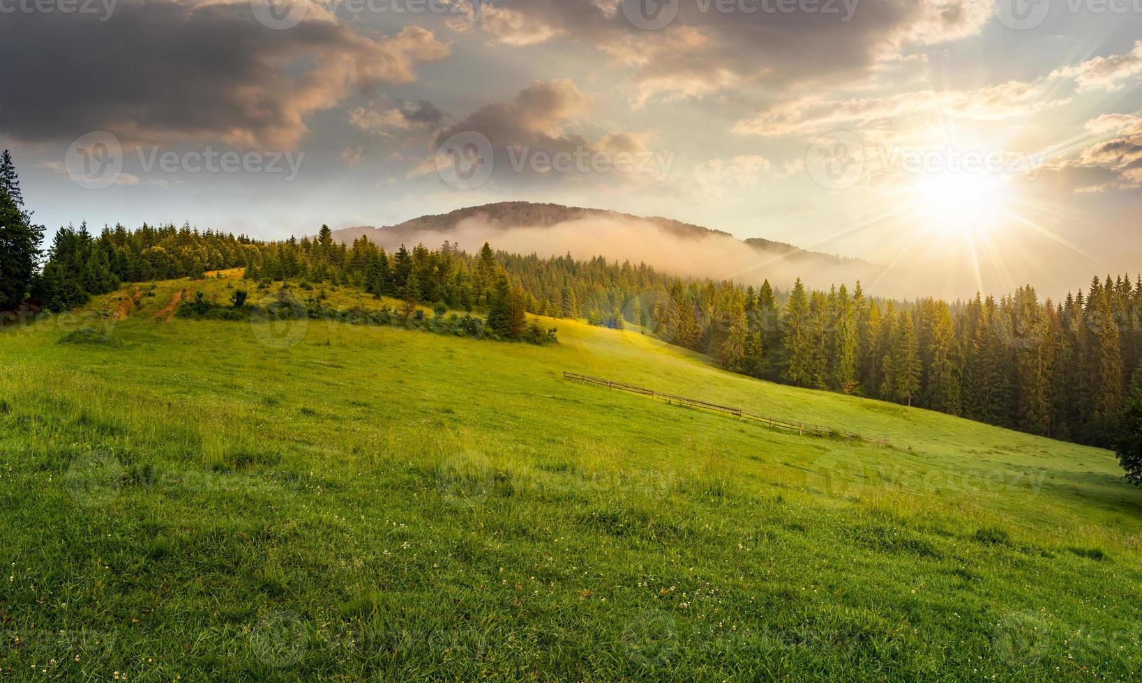 brouillard autour du sommet de la montagne au coucher du soleil photo