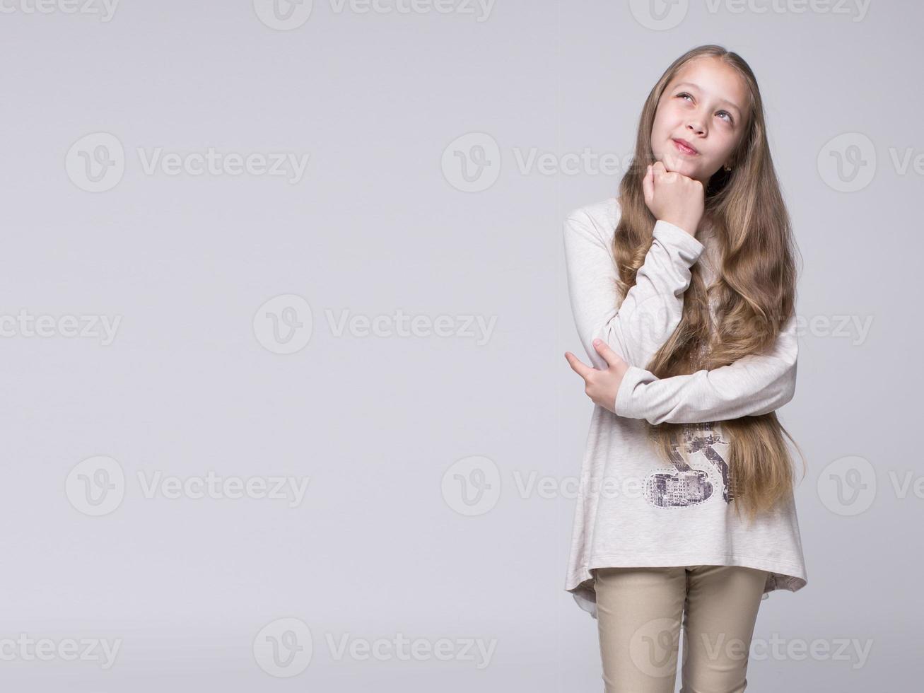 Portrait d'adolescente désorientée, debout sur un fond gris photo