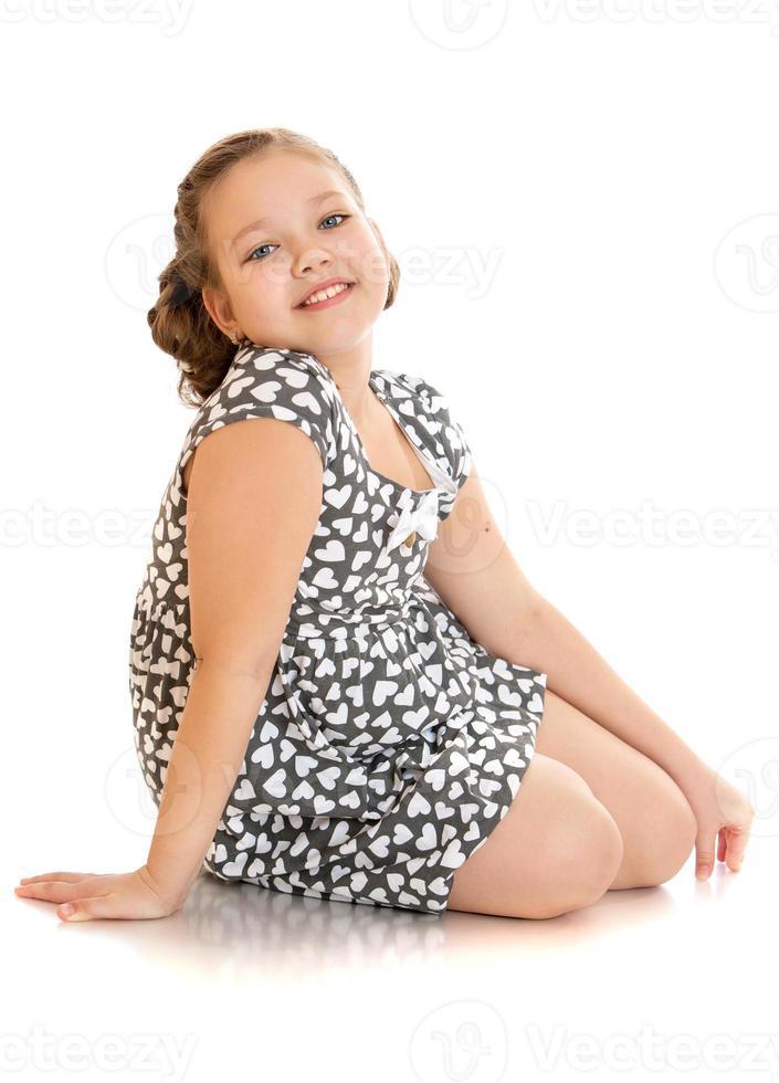 fille gaie en robe d'été assis sur le sol photo