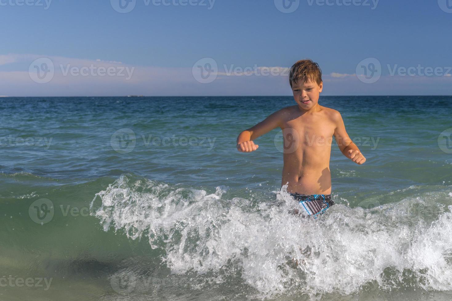 garçon qui traverse les vagues à la plage photo