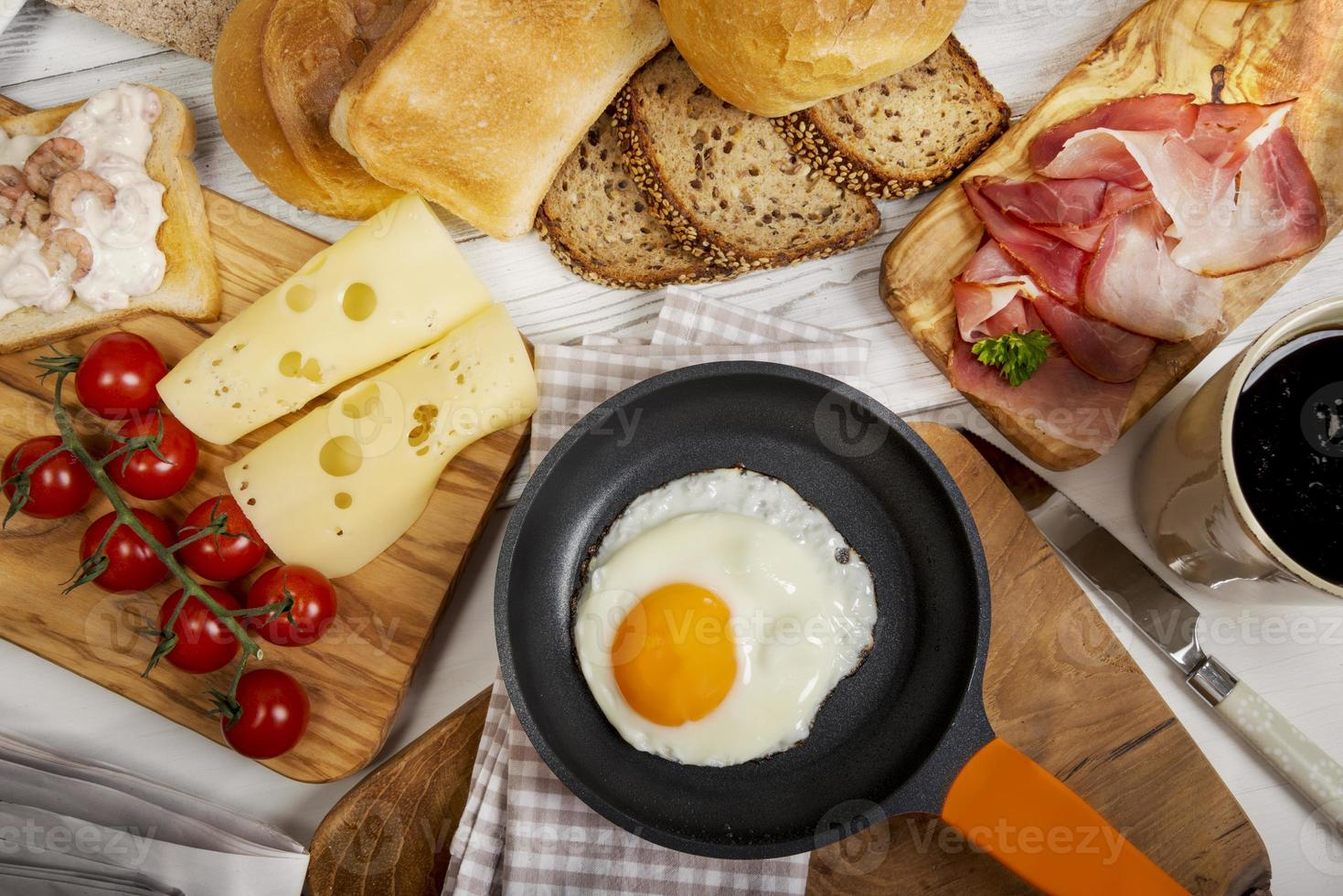 œuf au plat dans la poêle, fromage, jambon, pain et brioches photo