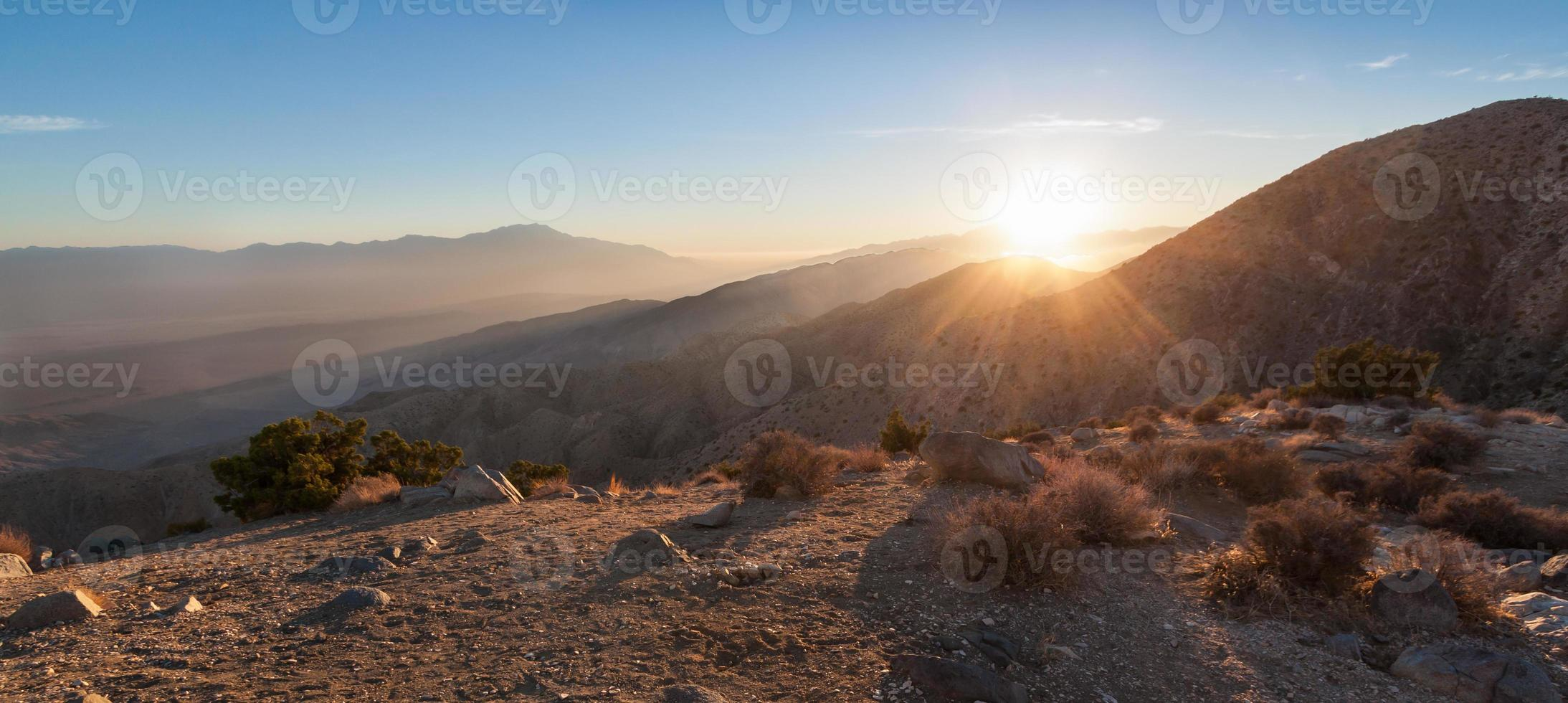 rayons de soleil sur la chaîne de montagnes dans le désert photo