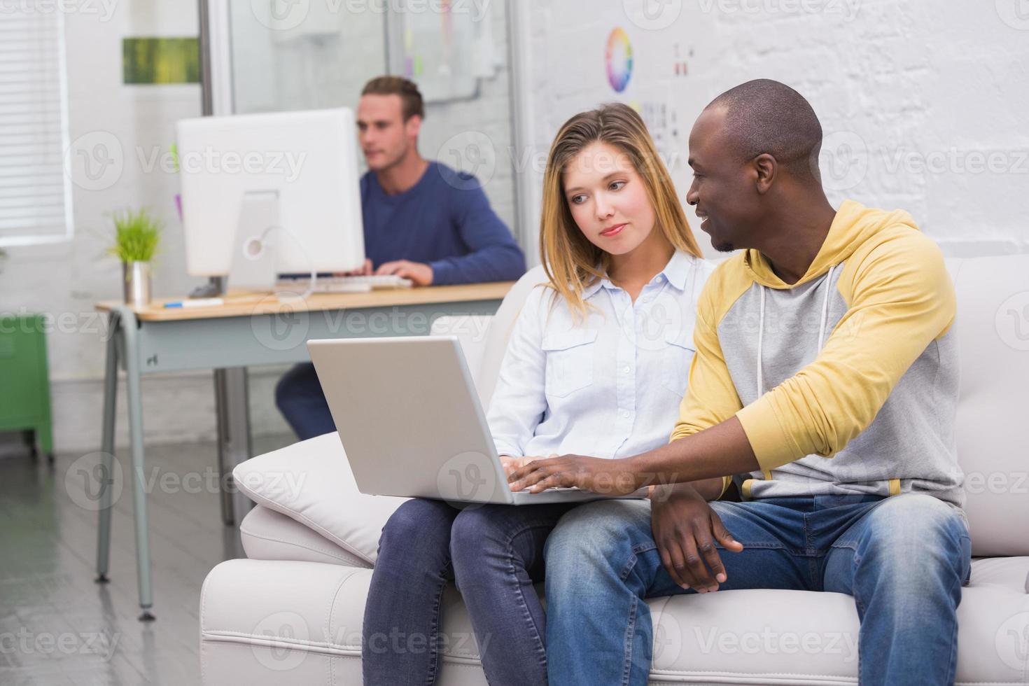 collègues occasionnels utilisant un ordinateur portable sur un canapé au bureau photo
