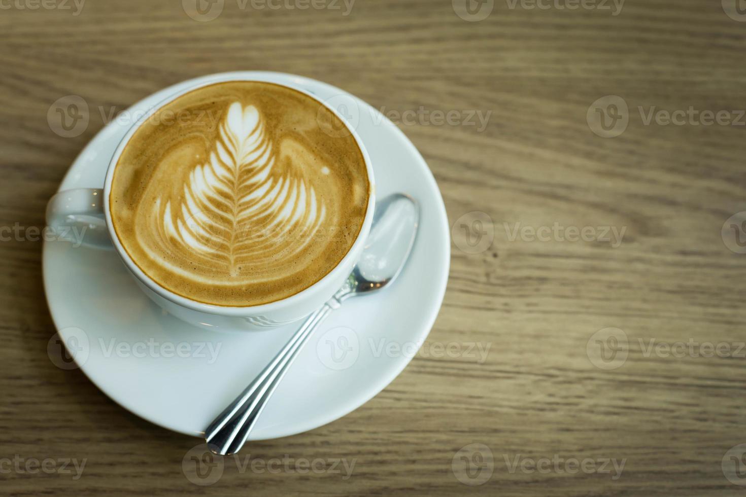 café latte art chaud dans une tasse sur la table en bois photo