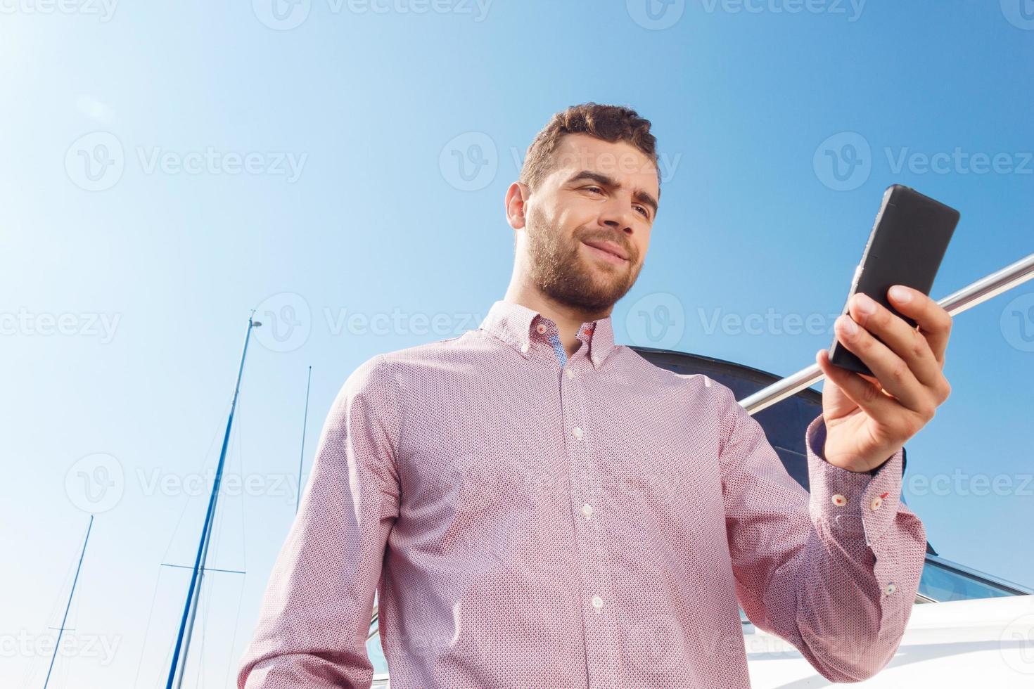 homme agréable tenant un téléphone mobile photo