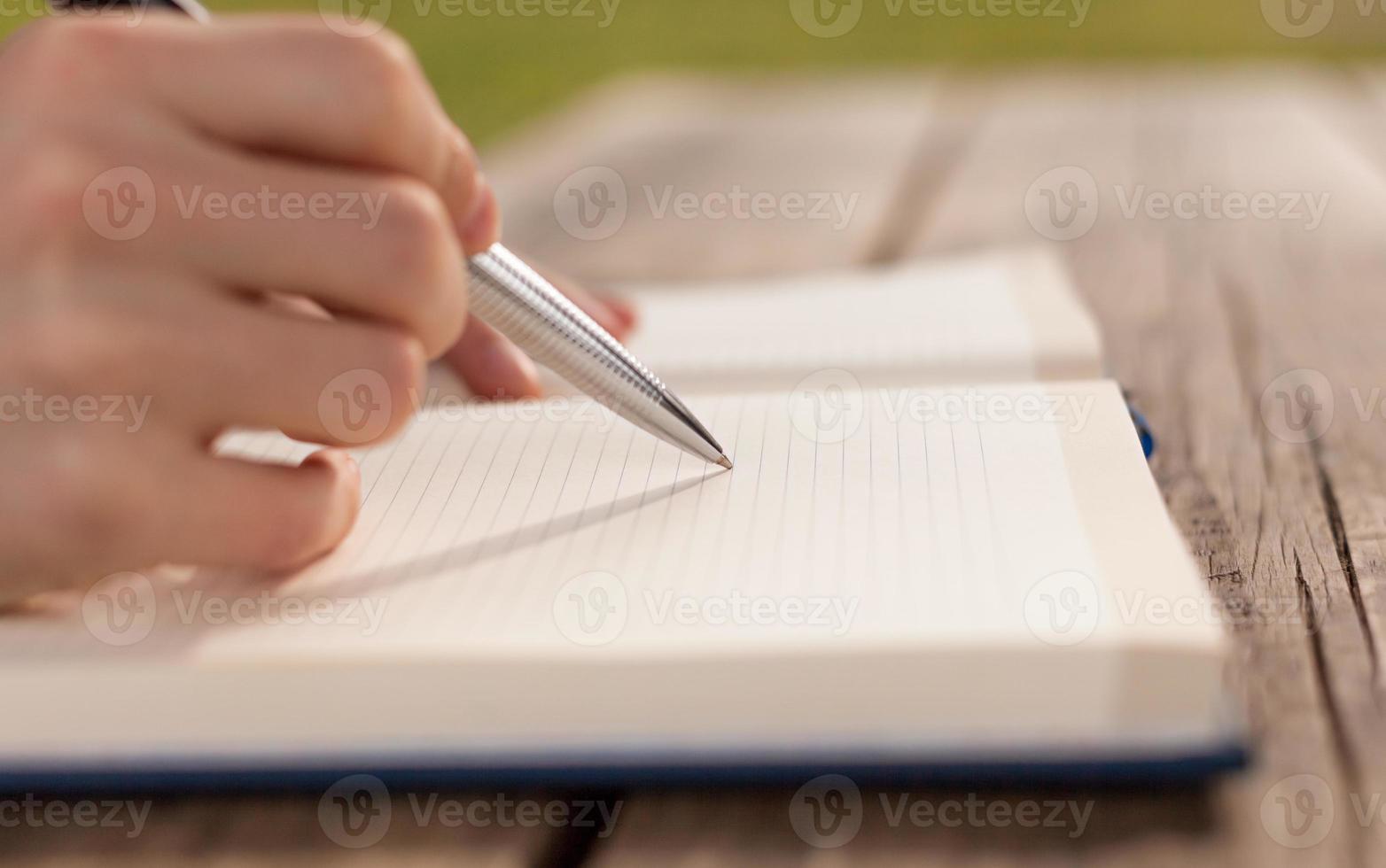 gros plan de l'homme écrit des notes sur la table en bois. photo