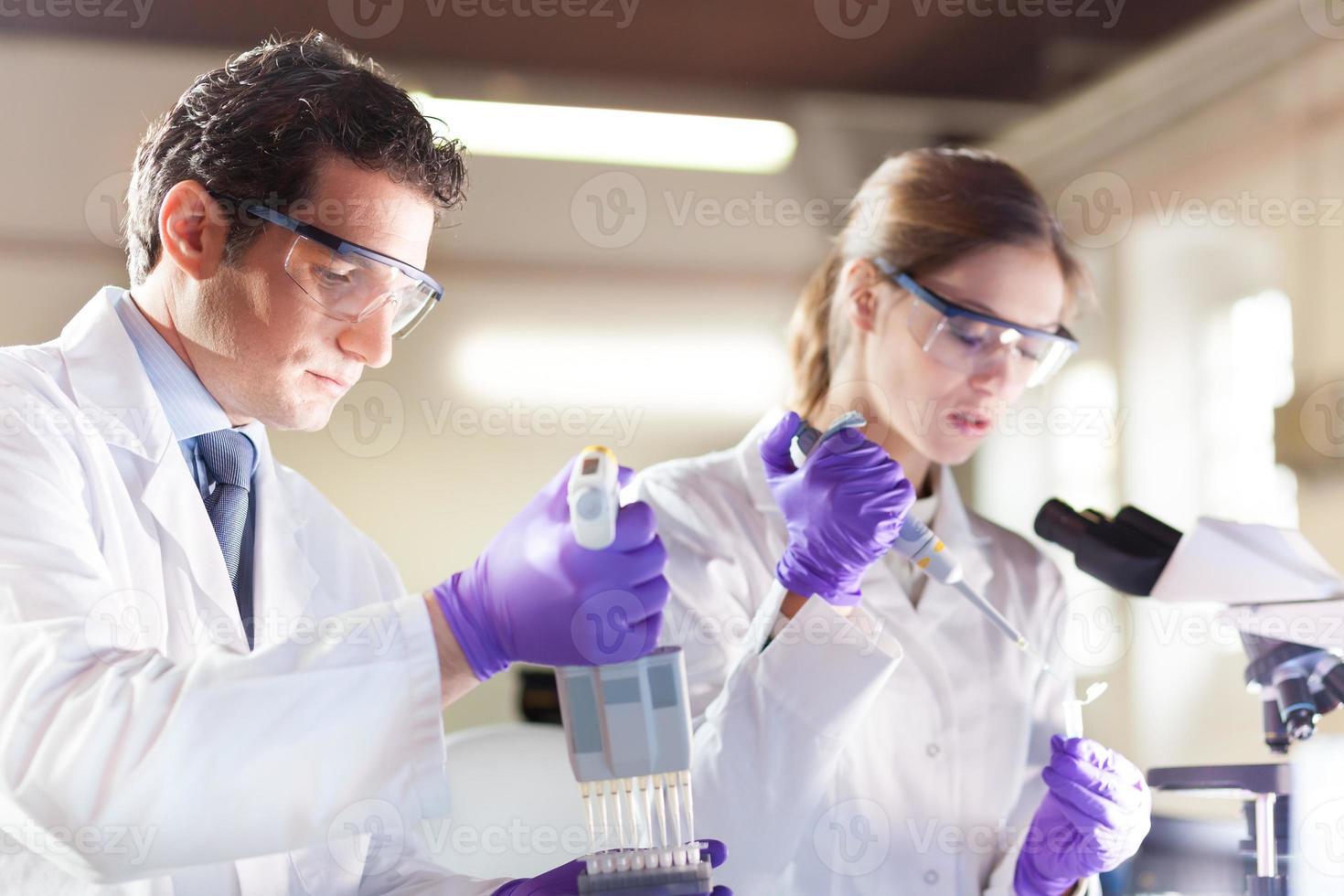 pipetage de jeune scientifique attrayant. photo