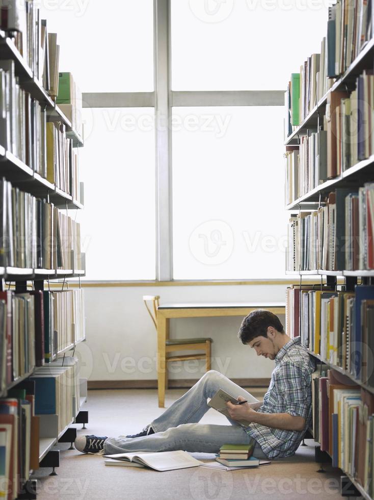 étudiant en lecture dans la bibliothèque photo