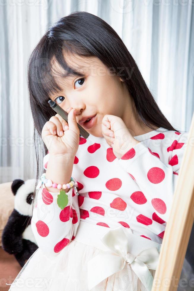 kid fille écrit sur tableau blanc avec stylo marque noire. photo