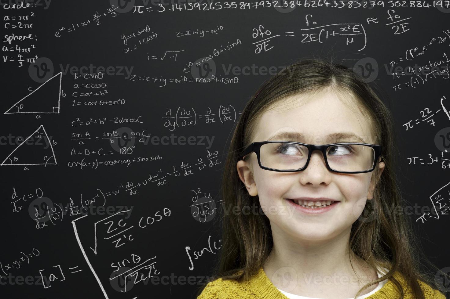 jeune fille intelligente se tenait devant un tableau noir photo