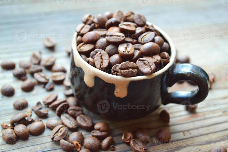 tasse pleine de grains de café sur la table en bois photo
