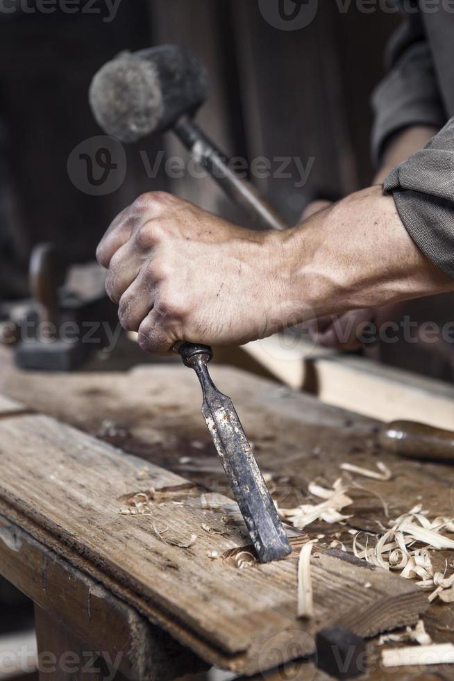 mains de charpentier avec un marteau et un burin photo