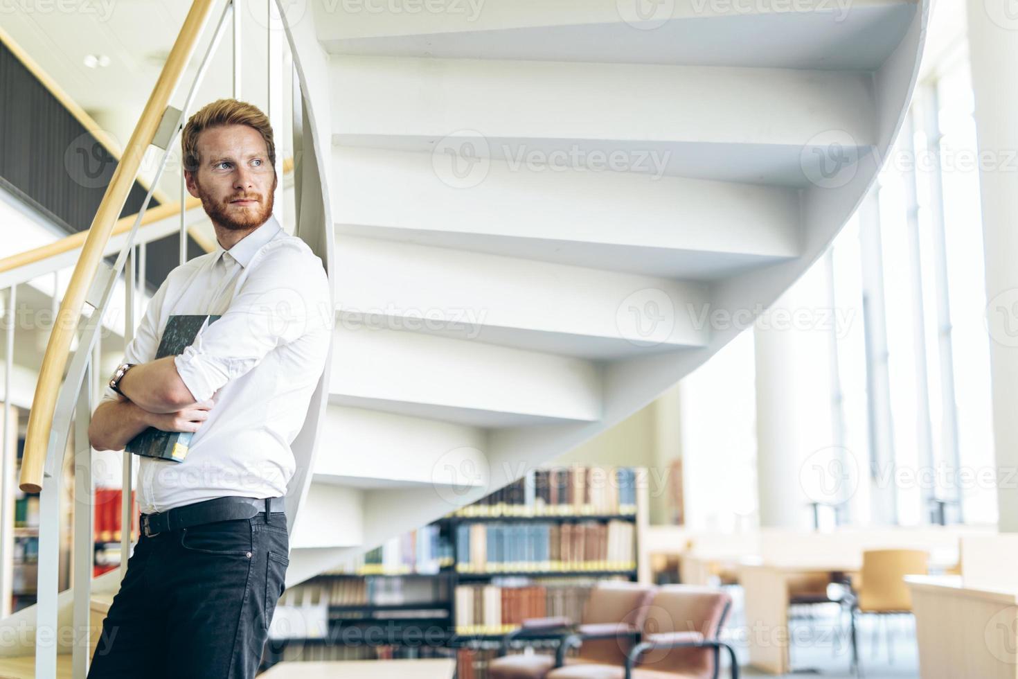 beau mec intelligent lisant un livre dans une bibliothèque photo