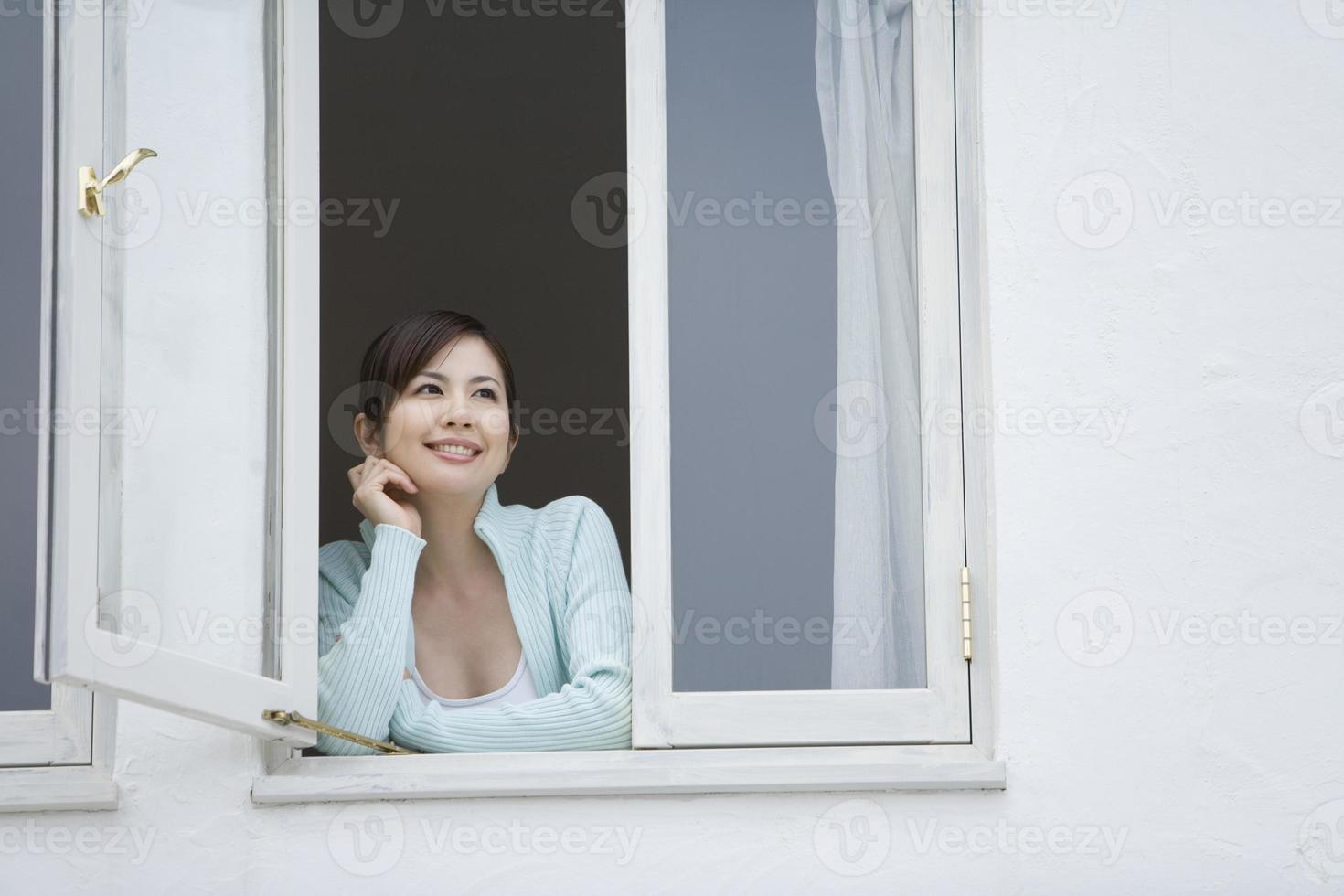 femme souriante, par, fenêtre photo